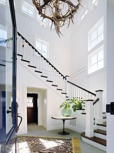 Dramatic white entry with antler chandelier and staircase in Napa Valley farmhouse by Ken Fulk in C Magazine