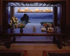 morrocan style metal studs, rustic carved wooden table, dark wood bifold doors opening to an incredibly magical view, trimmed with lilies and candles