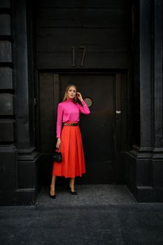 NYC Fashion Blogger Mary Orton in Milly fuchsia pink bow-tie blouse, orange Tibi pleated midi skirt, Dolce & Gabbana small black sicily bag, Saint Laurent classic black pumps and beaded leather belt