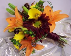 I designed this fresh floral bouquet for a fall wedding last year.  I love the bold and bright colors.  The chocolate brown coiled wire adds a touch of fun and mimics fern buds which are very pricey if you want them fresh. I am especially proud of this one because I entered it in an online wedding bouquet contest sponsored by The Floral Design Institute in Portland, Oregon and I won first place.  It's really nice to be recognized by your peers!