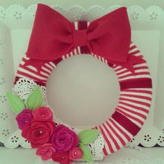 "Sew a little love. ""a polystyrene wreath base covered in a pair of stripy socks! I wrapped some wool around it to give a little texture. I then added a bow made from felt, some doilies, and a few felt roses, made from scraps of left-over felt."""