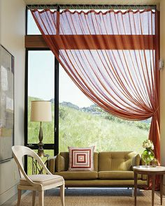 sofa in front of window cozies it up, love the style of drapery and rope at top