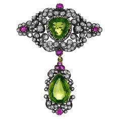 Antique Silver, Gold, Peridot, Diamond and Ruby Pendant-Brooch   Topped by a modified cartouche-shaped mount of stylized garland motif, centering one modified pear-shaped peridot approximately 3.30 cts., suspending one pear-shaped peridot approximately 6.45 cts., set throughout with 103 cushion-cut diamonds approximately 3.40 cts., accented by 8 cushion-shaped rubies, one diamond missing, approximately 10.7 dwt. Victorian or Victorian style