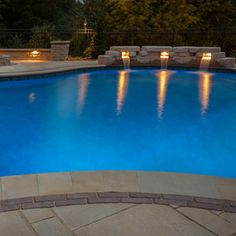 Beautiful lighting and waterfalls with this vinyl liner swimming pool. #vinyllinerpools #soncopoolsandspas #swimmingpools #backyard #outdoors