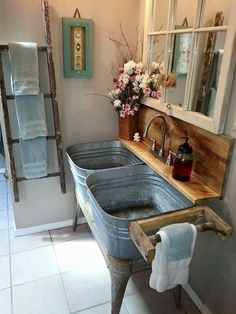 Rustic bathroom vanity using metal tubs for sinks and ladder for towel holder.