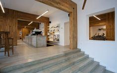 Šedý beton použili architekti na podlahu i schody, ale také na dlouhý pult.