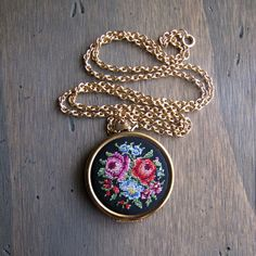 This is one of the prettiest necklaces I have ever seen! Made by Avon for their 1977 ad, its official name is The Floral Point Locket Necklace. The front of the locket is covered in black fabric, embroidered in petit point style with a boquet of roses and other flowers in rich vivid colors. This locket is in such great vintage condition, most likely hardly ever worn. The inside of the locket is marked AVON (see last photo). 33 inch gold tone cable chain with a c spring clasp. Locket is…