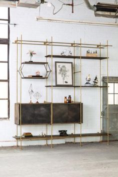 The Collector's Shelving system in brass and oak. By Amuneal.