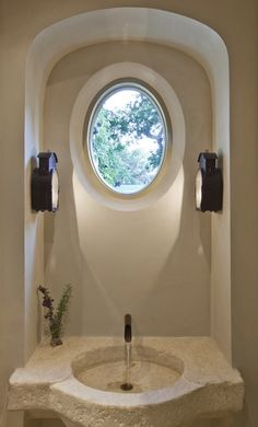 Gorgeous bathroom with rustic plaster walls and an recessed arch with porthole window.