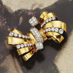 18 KARAT GOLD AND DIAMOND BOW BROOCH, VAN CLEEF & ARPELS, PARIS, CIRCA 1940.  The bow-knot of polished gold decorated with 65 old European-cut diamonds weighing approximately 6.40 carats, mounted in 18 karat gold and platinum, signed Van Cleef et Arpels, numbered 54787, assay marks.