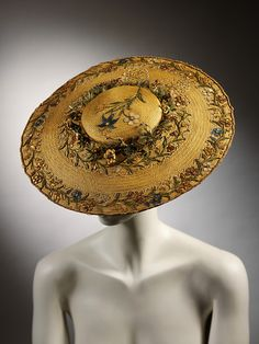 The V&A; says ~ Round, flat straw hat with shallow crown. Embroidered with straw-work flowers on crown and around brim; wreath of straw flowers around crown. Perhaps a recreation will appear at Flying Heart Millinery?
