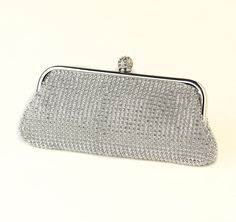 This Glamorous Crystal Bridal Clutch will make you feel like a princess or a movie star!  Clutch features a decorative rhinestone embellishment that will sparkle and shine!  Has silver plating and a round rhinestone encrusted closure and also features a pocket and shoulder strap chain inside.  Perfect for weddings, proms or a night out on the town!