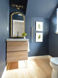 Paint: Benjamin Moore 'Hale Navy' | Vanity: GODMORGON/ODENSVIK by IKEA | Faucet: LUNDSKÄR in black by IKEA | Door and Drawer pulls: LANSA by IKEA | Mirror: Vintage/second hand | Vanity legs: Hairpin | Sconce: Antique brass Feiss | Artwork: The Graphics Fairy | Paint on Mirror/Pulls/Legs: Krylon Short Cuts 'Gold Leaf'