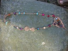 This is an organice wire formed necklace I made using gems and copper coloured wire, one of a kind and totally different.