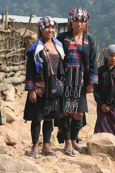 Akha tribal ladies in Laos. The Akha are an indigenous hill tribe who live in small villages at higher elevations in the mountains of Thailand, Burma, Laos, and Yunnan Province in China. They made their way from China into Southeast Asia during the early 20th century. (V)