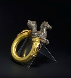 Ring in the form of a Hippocampus: Gold and silver with two garnet gemstones, cut en cabochon. Hellenistic, 3rd - 2nd Century BC. L. 3.8 cm, W. 2.8 cm, Inner diam. ring: 1.7 cm. © 2013 BADER ANCIENT ART Photo ©CLAUDIO BADER