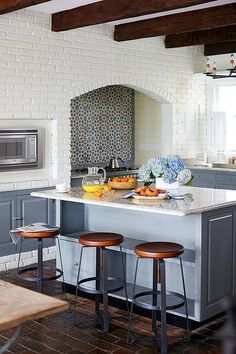 Beautiful kitchen features a ceiling accented with rustic wood beams situated over a white brick wall fitted with an arched alcove filled with a stainless steel stove under a blue mosaic tiled backsplash next to an integrated microwave.