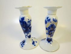 Antique Avon Flow Blue Candlesticks Myott Staffordshire Porcelain Candle Holders Flow Blue Porcelain Candle Holders Gilt Spidering Classical Shaped Flow Blue Porcelain Candlesticks with 2.5 inch flange drip guard Gilt Spider Web Hand Painted Details Raised Scroll Details Signed w/ unreadable Flow Blue symbol on bottom Size: 6.5 inches ht. 3.5 inch diameter base Date from 1900s Condition: Very Good, slight wear to gilt trim; One candlestick is slightly different from the other, variation...
