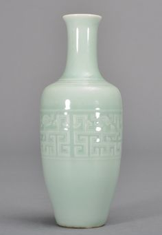 A SMALL CELADON-GLAZED VASE. The vase is tall and gourd-shaped. The exterior is decorated with imperial designs. The bottom is decorated with a marked seal. The vase is celadon glazed color. 7 5/8 in. tall. Qing Dynasty