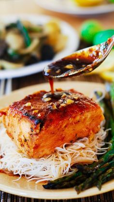 Asian salmon with gluten-free rice noodles and asparagus. Moist and juicy salmon, marinated, baked, and broiled in Asian garlicky glaze. Served with your favorite greens: