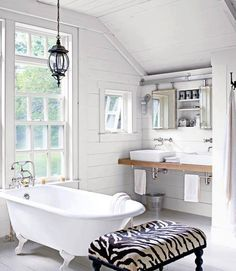 Zebra-print #ottoman sidles up to this cast-iron tub in the master #bath, outfitted with white china #sinks! The #mirrors #slide open, #barn #door—style, to reveal a recessed medicine #chest.