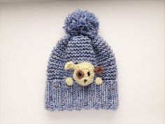 Knit kids pom pom hat with crochet puppy applique sewn onto. Fun winter outfit for kids Size: One size will fit from child up to teens (19-22; 49-55cm) Color: Blue with ivory/ brown applique Materials: wool acrylic blended yarn. This hat is READY TO SHIP! Please read my SHOPS POLICIES about