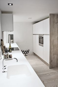 Køkkenet er ikke så stort, men er til gengæld praktisk indrettet med rene, hvide flader og en praktisk skabsvæg. Copenhagen Bath har leveret vask og bordplade i corian. Armatur fra Vola.