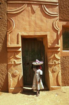 Africa | A young girl stands in front of a traditionally decorated Hausa house.  Agadez, Niger. | ©Michel Renaudeau