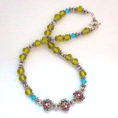 Royal Daisies - $30.00 - Beautiful hand-crafted necklace, lampworked murano florals paired with green Czech spacers and classic Bali texture beads. Sterling silver-plated, toggle. Approximate fastened length, 18 inches. #jewelry #handcrafted #diy #necklace