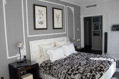 Weiße Zierstuck-Rahmen und graue Wand im Schlafzimmer
