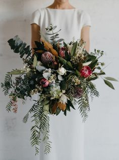 crazy wild bouquet with lot's of greenery and king protea. Great bouquet for a boho wedding or modern wedding with edgy details