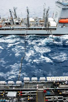 The Military Sealift Command fleet replenishment oiler USNS Henry J. Kaiser (T-AO 187) sends fuel hoses to the aircraft carrier USS John C. Stennis (CVN 74) during a replenishment-at-sea.
