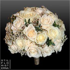 Elegant och kompakt rund brudbukett i hållare, i creme och vita toner, med rosor och vaxblomma.