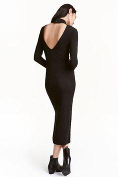 Трикотажное платье : Облегающее трикотажное платье с длинным рукавом. На платье низкий воротник стойка и треугольный вырез сзади с застежкой у горловины. По бокам разрезы.