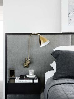 Renovation: the overhaul of an art-loving, empty-nester's Melbourne apartment: Lighting plays an important role in this home, with interesting and intricate detailing — including this exposed lamp attached to the bedroom headboard.