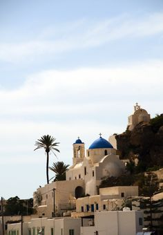 Traditional white chapel with blue dome on Ios island