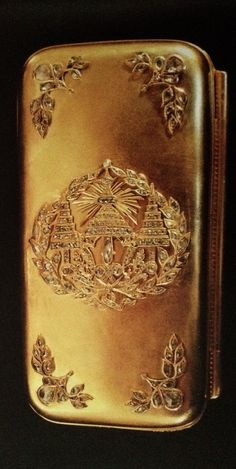Gold cigarette box embossed with the Royal insignia of a crown set with diamonds.