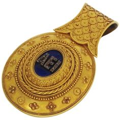"18K yellow gold bulla with central blue enameled plaque with AEI (Greek for ""forever"") in diamonds. 1867"