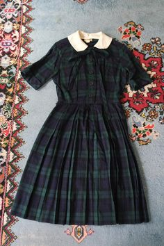 A dress that really makes you think 50s! Cute designer Nelly Don wool plaid day dress in the classic 1950s style. Detachable collar if youre not into it. Two ties at the neckline. Buttons up the front with hook/eye closures at the waist. Pleated skirt. This dress is in excellent vintage