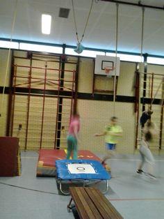 Springen in de trampoline en proberen de tas die in de touwen hangt te raken.