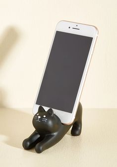 Keep a keen eye on your digital companion by entrusting it to this charming black cat by Japanese Gift Market! Stretching out on your desk or bedside table, this functional feline holds your smartphone upright with a small notch on its back and cute curled tail. Allowing you to display adorable snapshots of your favorite furry friend or free your paws to type while you talk, this sweet accessory is a perfectly playful way to keep your habitat tame and tidy!