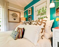 turquoise bedroom wall, white bedding and a mix of pillows, white bedside tables; gold, yellow, coral accents...loving the colors!