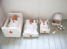 TOY HOSPITAL // patients (dolls), beds + bedding, medication (sweets in pots), doctors/nurses bag (little suitcase for supplies), stethiscope , plasters, spoons, cups (for giving water), outfits for the kids, bandages, patient charts (basic info kids can imagine), syringe, thermometer...