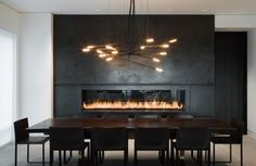 Dining room: eye level fireplace, modern eye catching fixture, long dining table