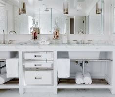 Spa-like bathroom with custom vanity and built-in mirror with inset sconces. Double sinks with gooseneck facuets and marble countertops. Glam touch with mirror fronted drawers and nickel towel racks and shelves.