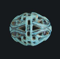 AN EGYPTIAN FAIENCE OPENWORK WADJET-EYE BEAD THIRD INTERMEDIATE PERIOD, DYNASTY XXI-XXV, 1070-712 B.C. Turquoise blue in color, with details in black glaze, with four pairs of wadjet-eyes in four zones, arranged with the tops of each pair adjacent to each other
