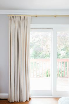 floor-to-ceiling curtains from The Shade Store: Tailored Pleat Drapes in a linen blend (the color is Alabaster). sleek and simple rod, the Madison in a gold finish.  https://www.theshadestore.com/drapery/custom-drapes/tailored-pleat-drapery  https://www.theshadestore.com/drapery/drapery-hardware/madison-drapery-hardware/customize