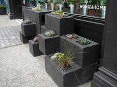 Jardineira de bloco de concreto na calçada de uma loja em Londres.