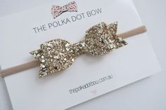 Gold glitter lola bow  Bow is attached to a soft nylon headband - super soft & stretchy OR a partially lined alligator hair clip  Choose from a nude(as pictured), white, ivory, light pink, navy or black headband!  Bow is made from premium non-shedding glitter fabric & measures approx 3.5 inches (9 cm)  *Nylon headbands grow with your baby & are made to fit newborns all the way up to adults!  Follow // Share Follow us on Instagram for coupons/giveaways @thepolkadotbowco &  Share your pics…