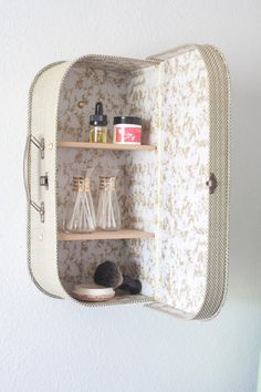 DIY old kid's size suitcase mounted on the wall as a cabinet